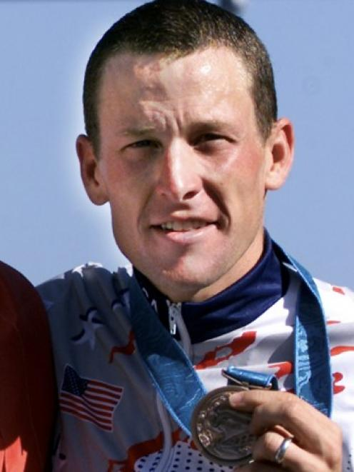 Lance Armstrong poses with his bronze medal after the men's Olympic individual time trial in...