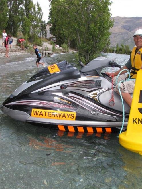 Launch warden Craig Blake prepares to install a buoy in Lake Wanaka at Penrith Beach yesterday to...