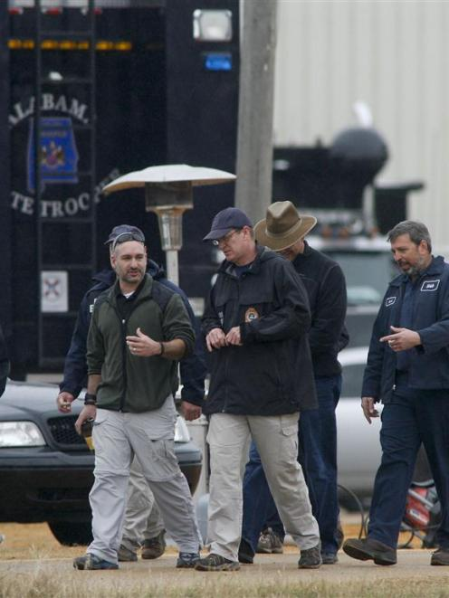 Law enforcement officials near the bunker where the boy was held.  REUTERS/Phil Sears