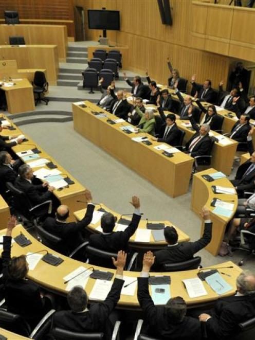 Lawmakers raise their arms to vote against the Bill to tax deposits in Nicosia this week.  Cyprus...