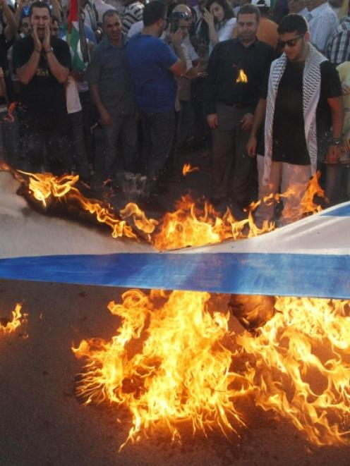 Lebanese and Palestinian protesters burn an Israeli flag during a demonstration to denounce...