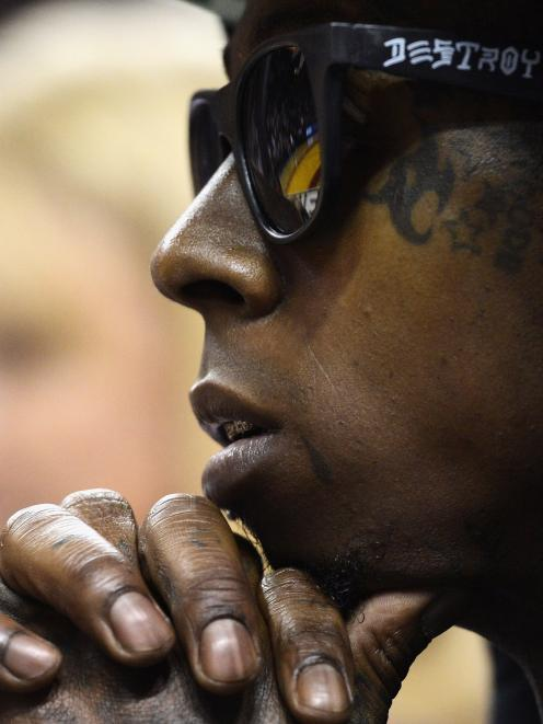 Lil Wayne watches the NBA basketball game between the Miami Heat and the Houston Rockets in Miami...