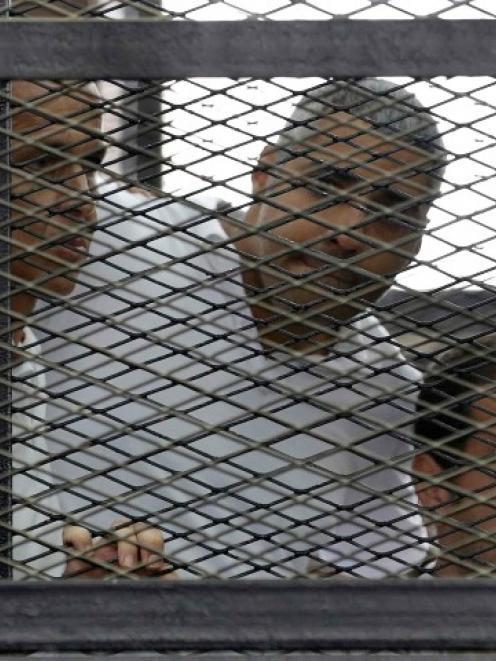 Listening to the ruling at a court in Cairo are (l-r) Peter Greste, Mohamed Fahmy and Baher...