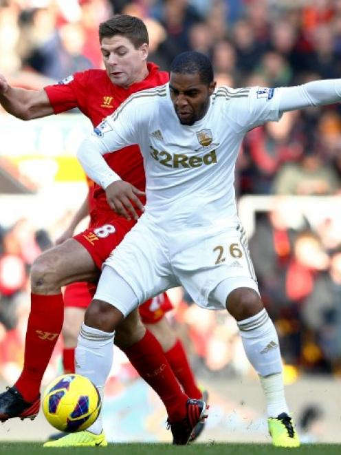 Liverpool's Steven Gerrard (L) challenges Swansea City's Kemy Agustien during their English...