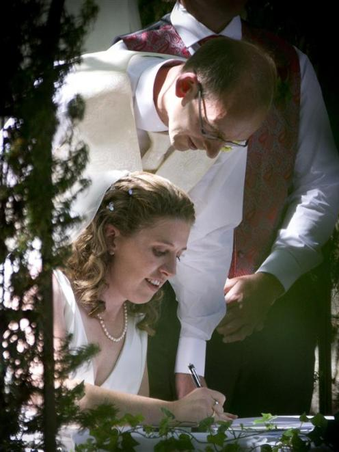Liz Davies and David Bain signing the marriage certificate after the ceremony of their wedding at...