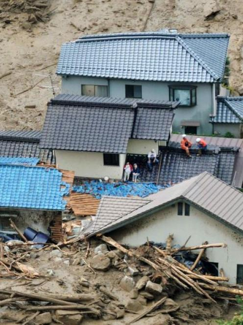 Local residents wait for rescue operation atop of collapsed houses as rescue workers stand by...