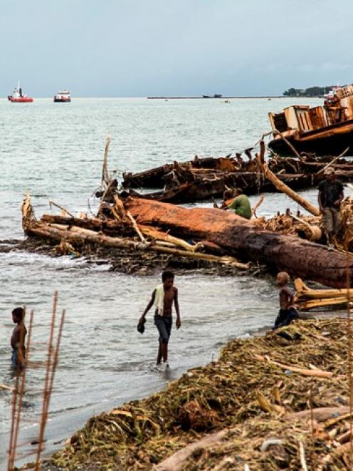 Locals walk among debris washed ashore after severe flooding near the capital Honiara in the...