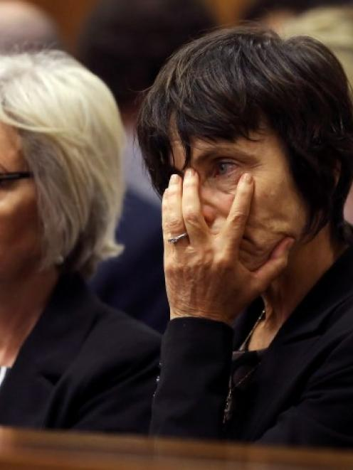 Lois Pistorius (L), the aunt of Oscar Pistorius, sits with an unidentified family member during...