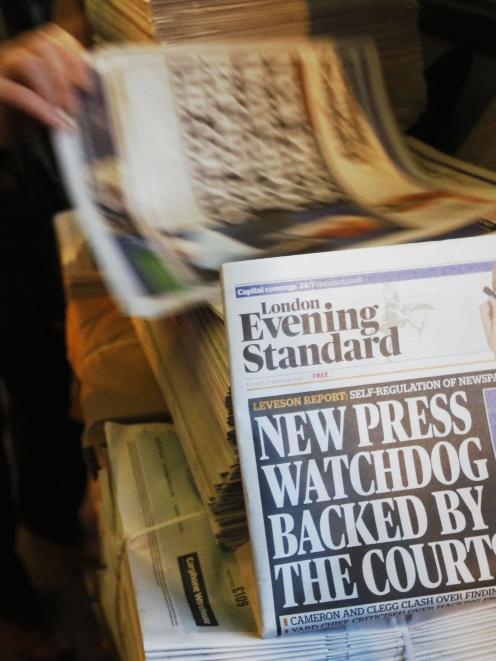 Lord Justice Brian Leveson appears on the front page of a stack of evening newspapers after his...