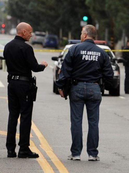 Los Angeles police and robbery homicide detectives investigate the scene where four people were...