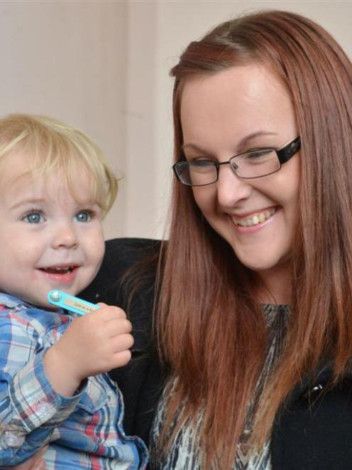 Lucas Pocklington holds a Baby Belly Button designer clip while mother Jayde Pocklington looks on...