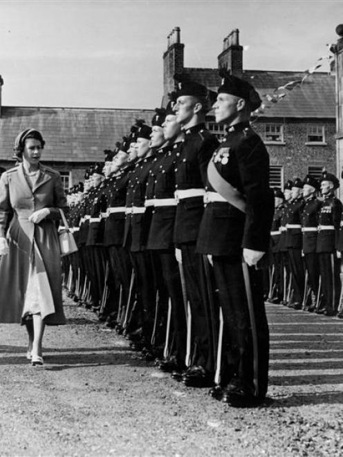 Major Dermot Neill, father of actor Sam Neill, inspects the troops with a young Queen Elizabeth...