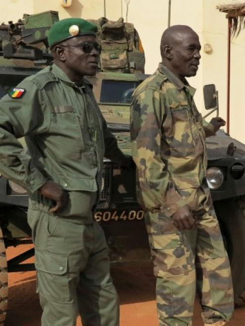 Malian military soldiers stand near an armoured vehicle belonging to the French Army at the...