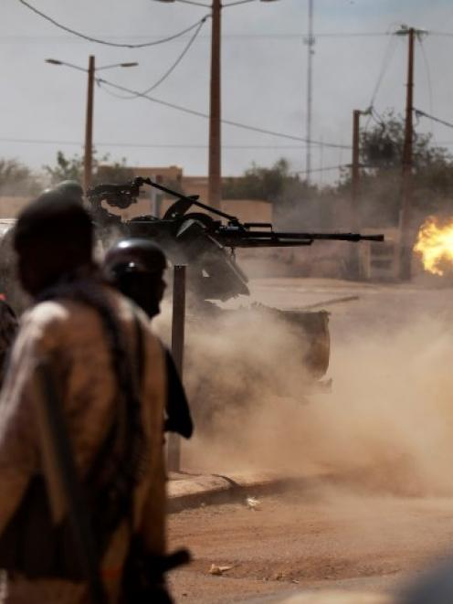 Malian soldiers fire a machine gun as they battle Islamists on the streets of Gao. REUTERS/Joe...
