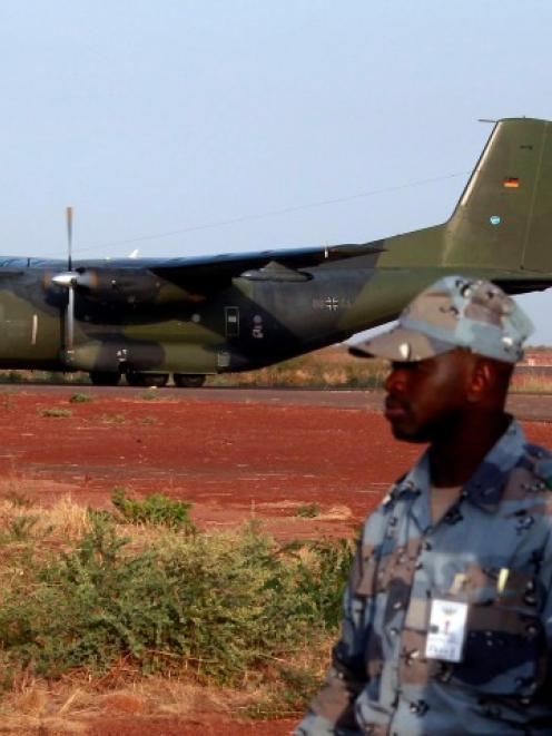 Malian soldiers stand guard while the first German military transall C-160 cargo lands in Bamako...