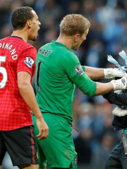 Manchester City's Joe Hart (C) prevents a supporter from reaching Manchester United's Rio...