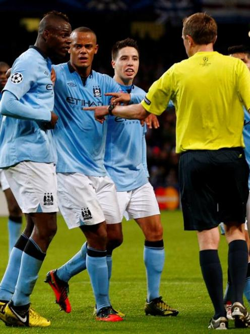 Manchester City's Mario Balotelli remonstrates with referee Peter Rasmussen after their Champions...