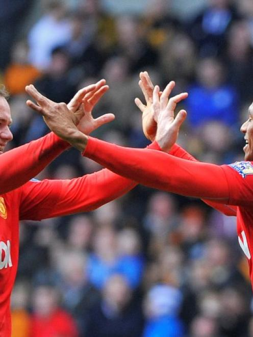 Manchester United's Antonio Valencia (R) celebrates scoring with teammate Wayne Rooney against...