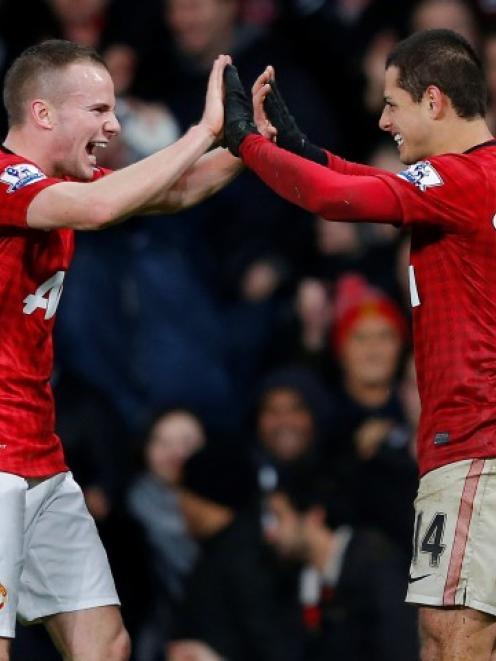 Manchester United's Javier Hernandez (R) celebrates with Tom Cleverley aftrer scoring during...
