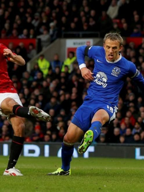 Manchester United's Ryan Giggs shoots to score past Everton captain Phil Neville (R) during their...