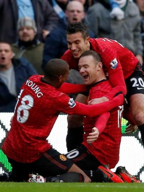 Manchester United's Wayne Rooney (C) celebrates scoring against Manchester City with Robin Van...