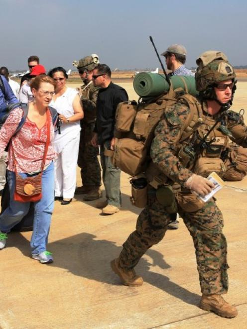 Marines guide US citizens down the flight line during a recent evacuation of personnel from the...
