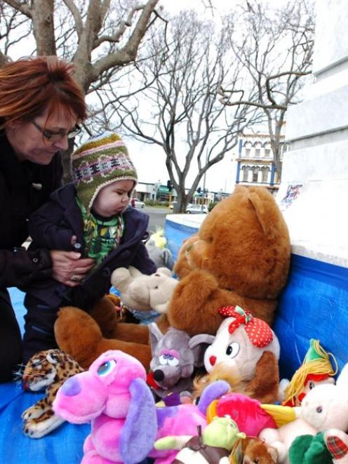 Mary Sharp and her grandson Leeroy Gillon-Reynolds (6 months) place a teddy bear at the base of...