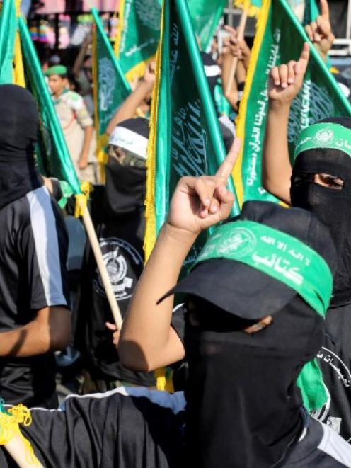 Masked Hamas members take part in a rally in support of the armed Palestinian factions, in Rafah...