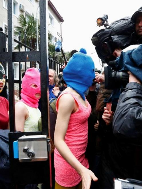 Masked Pussy Riot members leave a police station in Adler after they were detained on suspicion...