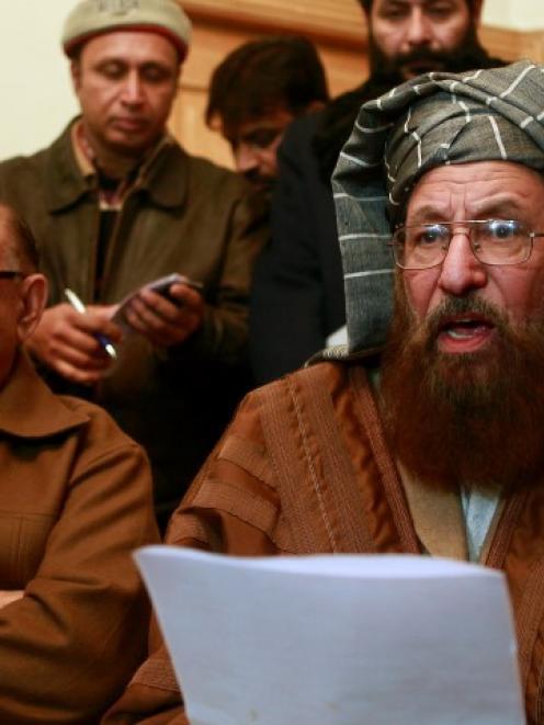 Maulana Sami ul-Haq (R), a Taliban negotiator, reads a joint statement with Irfan Siddiqui, a...
