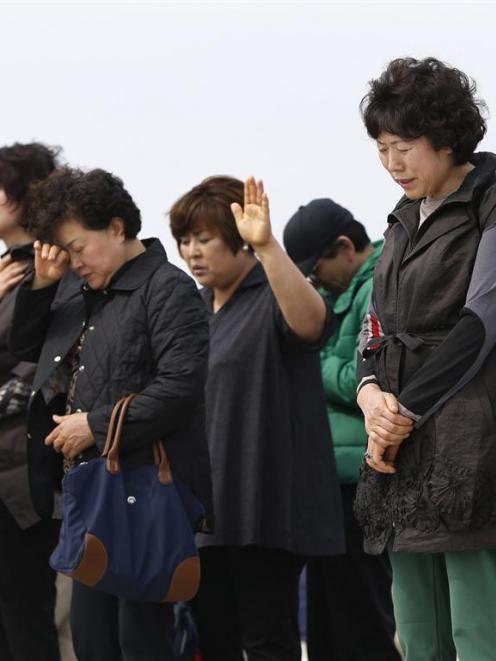 Members of a Christian group pray for missing passengers who were on the South Korean ferry Sewol...