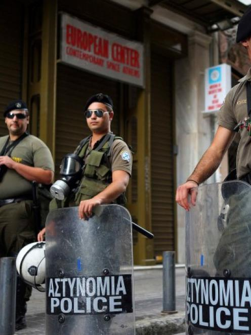 Members of a Special Police unit secure an area following the shootout in central Athens. REUTERS...