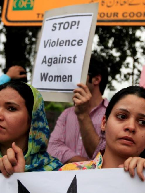 Members of civil society and the Human Rights Commission of Pakistan hold placards during a...
