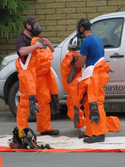Members of the Alexandra Volunteer Fire Brigade don bright orange chemical splash suits and...