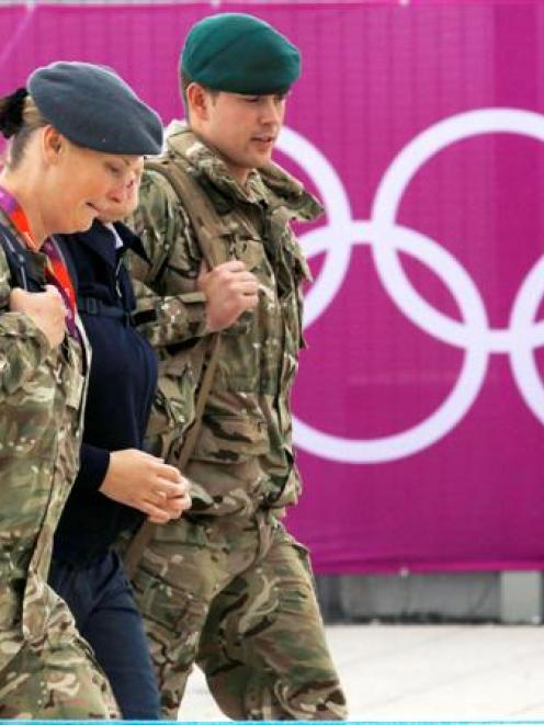 Members of the armed forces walk past the Olympic rings on the perimeter of the Olympic Park in...