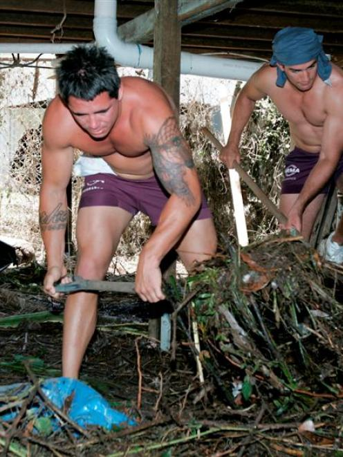 Members of the Brisbane Broncos rugby league team remove debris from under a house damaged by a...