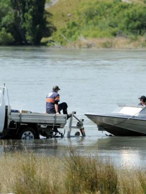 Members of the National Police Dive Squad, from Wellington, head out on the Clutha River to...