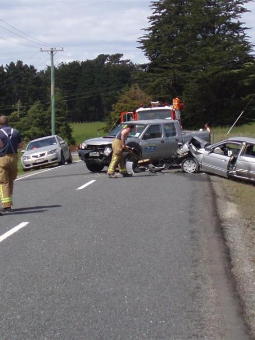 Members of the Owaka Volunteer Fire Brigade survey a two-vehicle crash on Purakaunui Falls Rd,...