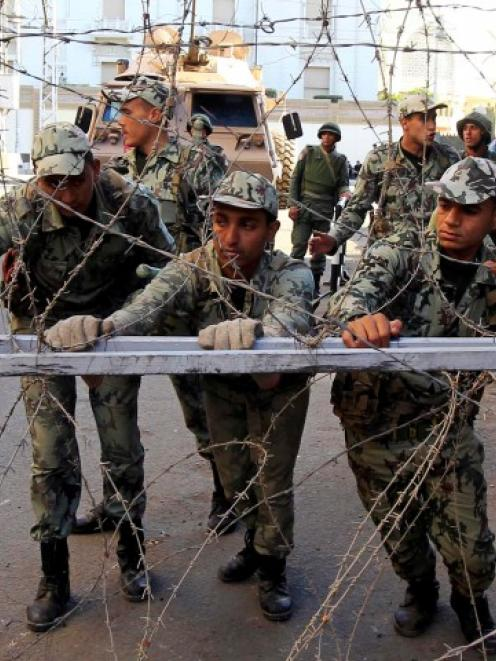 Members of the Republican Guard move barbed wire barricades to close a road leading to the...