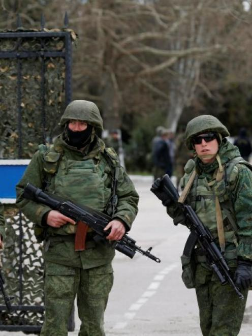 Men believed to be Russian servicemen stand guard outside the naval headquarters after it was...