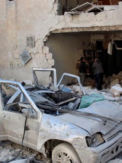 Men gather their belongings as a damaged car sits at a site hit by what activists said was an...
