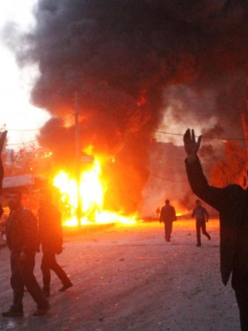 Men react near a site hit by what activists say are barrel bombs dropped by government forces on...