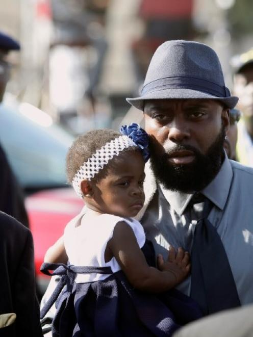 Michael Brown Sr. (in hat) attends the funeral for his son Michael Brown at Friendly Temple...