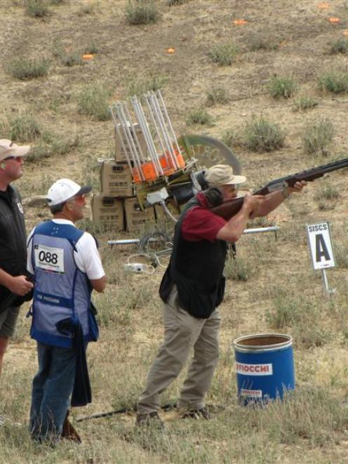 Michael Gould, of New Zealand, sights his target while Bruce Scott (left), of Auckland, Scott...