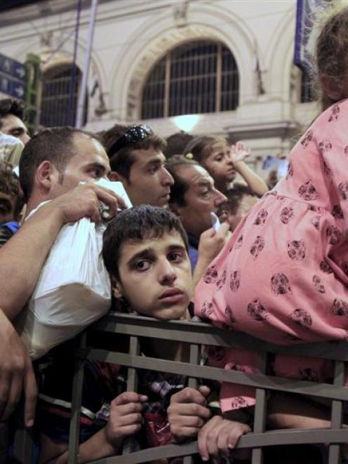 Migrants jostle for positions this week to board a train for the West from Budapest, Hungary.