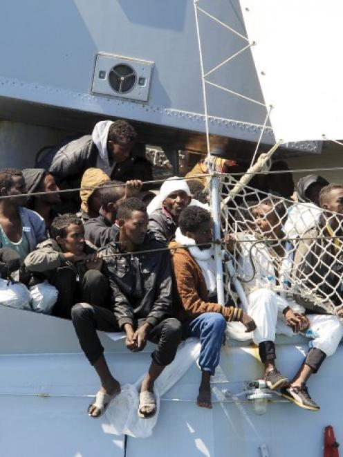 Migrants on board the Italian Navy ship Chimera wait to be disembarked in the southern harbour of...