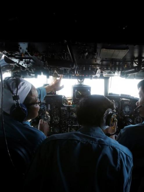 Military officers work in the cockpit of a Vietnam Air Force aircraft during the search for the...