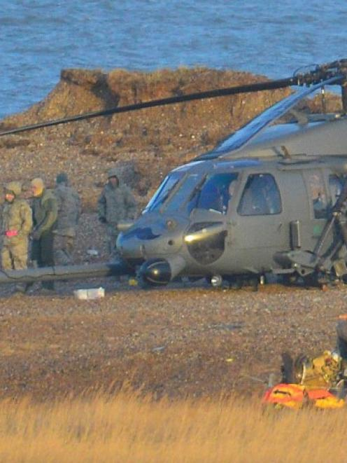 Military personnel and emergency services attend the helicopter crash scene. REUTERS/Toby Melville
