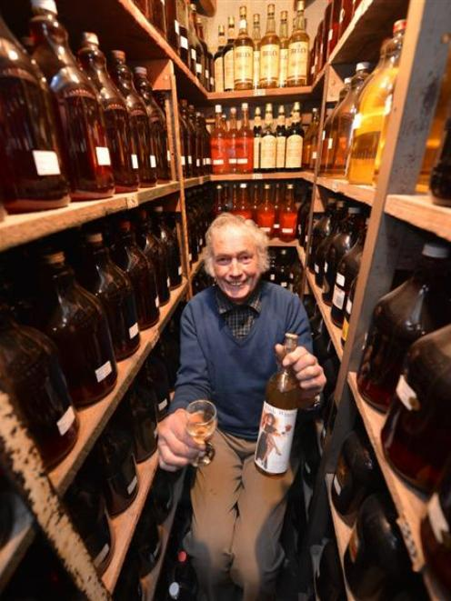 Milton wine-maker Colin Weatherall samples a 1976 crab-apple wine in a section of his cellar...