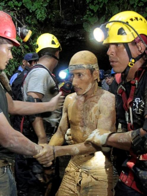 Miners and rescue workers hold a man (C) covered in mud after he was rescued from the gold mine...